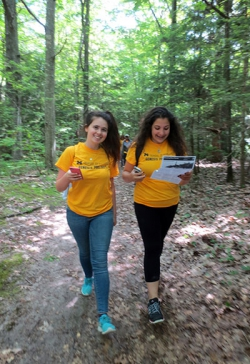 Mallory Baker checks a fitness app during the hike while Sara Elhasan navigates