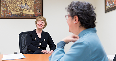 U-M School of Nursing Dean Patricia D. Hurn talk across the table to faculty member Megan Eagle