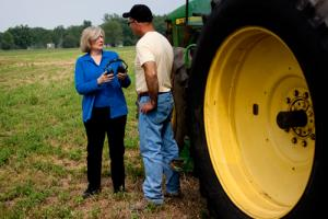A woman talks to a man outside by a tractor while holding a pair of headphones.