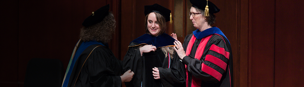 Student gets hooded at graduation by faculty member in robes.
