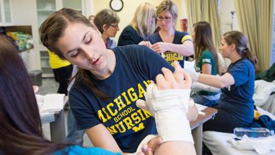Nursing student in tshirt wraps a cast around an arm