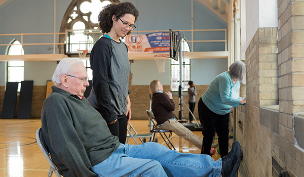 Woman looking at a older man sitting in a chair in a gym while doing research.