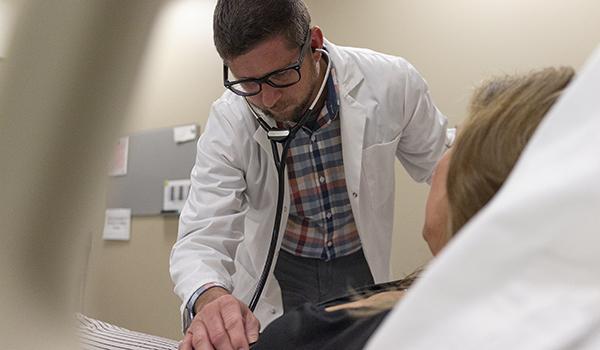 Nurse examines patient with stethoscope