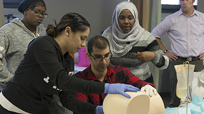 Four students with gloves on suture a mannequin