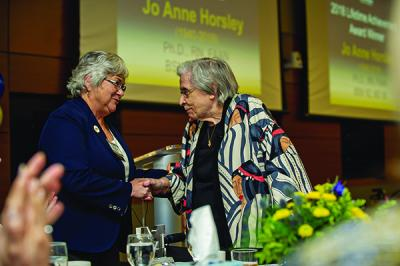 Joyce Crane (r) accepting Horsley's Lifetime Achievement Award from Linda Zoeller, president of UMSN's Alumni Society Board of Governors