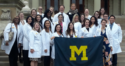 Group of students in white coats holding a block M flag