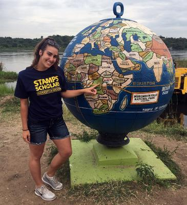 Student points to Africa on a globe while she's in Uganda.